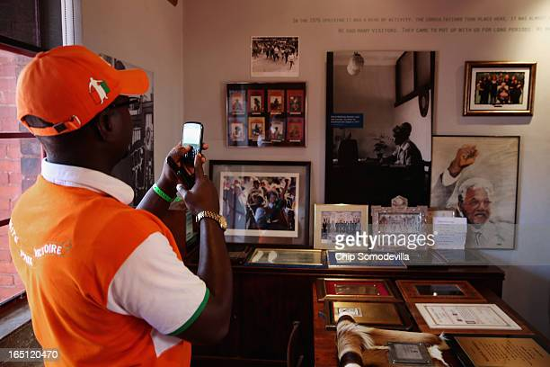 A tourist takes a photograph inside the Mandela House and Museum on historic Vilakazi Street in Soweto March 31 2013 in Johannesburg South Africa...
