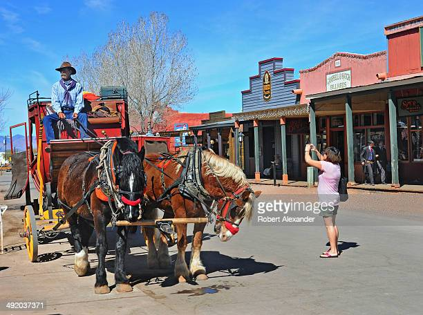 Tourist takes a photograph of a stagecoach driver in historic Tombstone, Arizona, known as 'The Town Too Tough to Die.' The town, featuring staged...