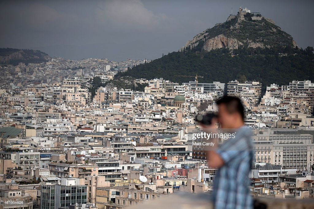 A tourist takes a photograph of Athens viewed from the Acropolis ahead of Greek's general election on January 22, 2015 in Athens, Greece. According to the latest opinion polls, the left-wing Syriza party are poised to defeat Prime Minister Antonis Samaras' conservative New Democracy party in the election, which will take place on Sunday. European leaders fear that Greece could abandon the Euro, write off some of its national debt and put an end to the country's austerity by renegotiating the terms of its bailout if the radical Syriza party comes to power. Greece's potential withdrawal from the eurozone has become known as the 'Grexit'.