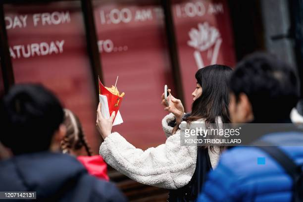 A tourist takes a photograph of her French fries cornet in central Brussels on March 14 amid the outbreak of COVID19 caused by the novel coronavirus...