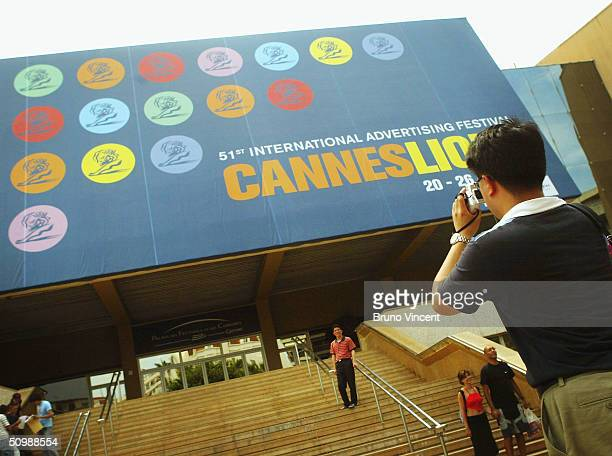 A tourist takes a photograph of the Palais des Festival entrance at the Cannes Lions International Advertising Festival on June 19 2004 in Cannes...
