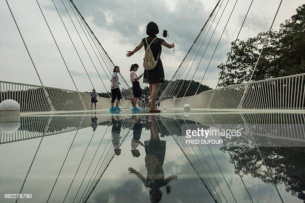 Tourist takes a photograph on the world's highest and longest glass-bottomed bridge above a valley in Zhangjiajie in China's Hunan Province on August...