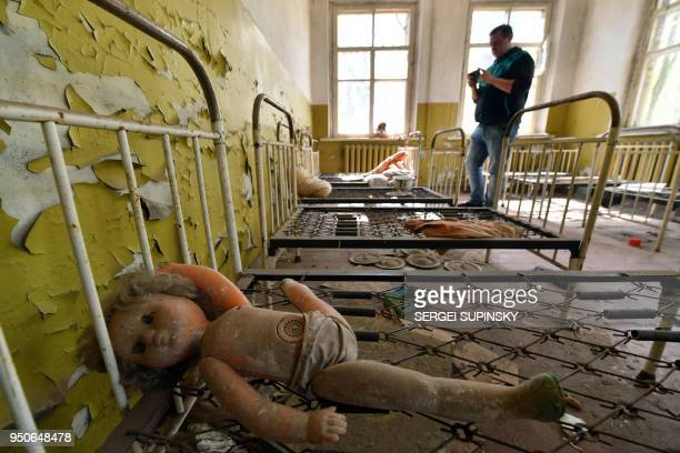 TOPSHOT A tourist takes a picture in an abandoned kindergarten in the ghost village of Kopachi near Chernobyl Nuclear power plant during their tour...