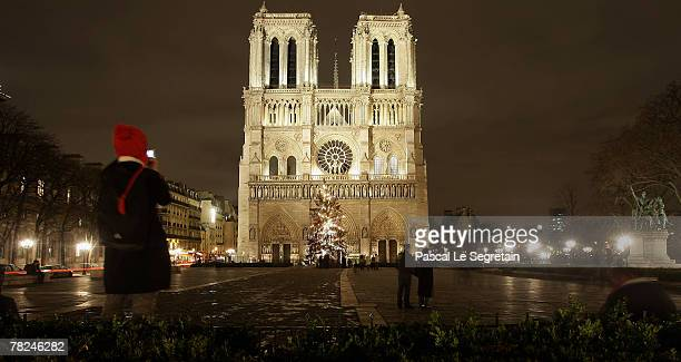 A tourist takes a picture of a Christmas tree illuminated in front of the NotreDame de Paris Cathedral on December 4 2007 in Paris France