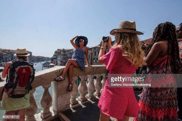 A tourist takes a picture of one of her friends at the top of Rialto bridge on August 1 2017 in Venice Italy Over 30 million tourists visit the 3...