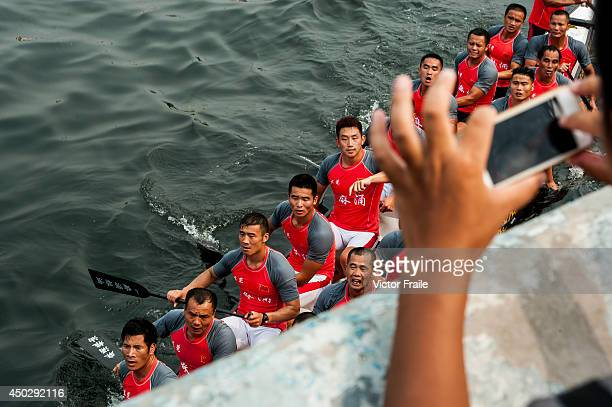 A tourist takes a picture of racers during Hong Kong International Dragon Boat Races on June 8 2014 in Hong Kong Hong Kong The dragon boat festival...