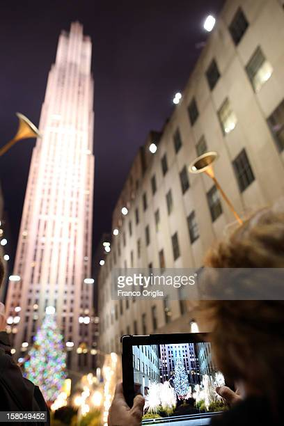 A tourist takes a picture of the Christmas tree at the Rockefeller Center on December 5 2012 in New York City Christmas holiday season in New York is...
