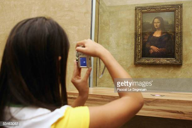 A tourist takes a picture of the famous Leonardo Da Vinci's painting The Mona Lisa in the Grande Galerie of the Louvre museum on August 24 2005 in...