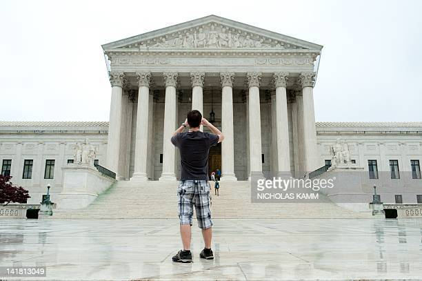 Tourist takes a picture of the US Supreme Court in Washington on March 24 two days before the court hears arguments on US President Barack Obama's...