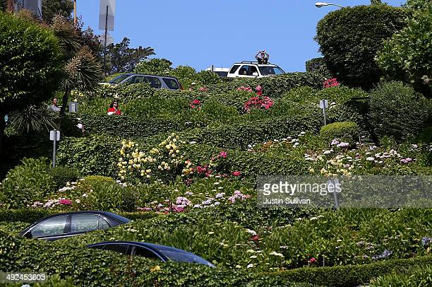 A tourist takes a picture out of a sunroof while driving down Lombard Street on May 20 2014 in San Francisco California The San Francisco Municipal...