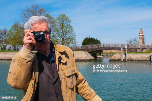 A tourist takes a picture sailing a canal on a boat of a fishing tour organized by Cooperativa San Marco in Burano on April 14 2018 in Venice Italy...