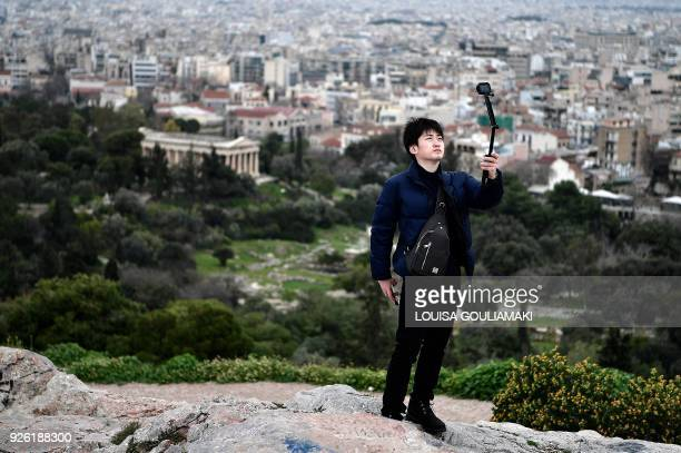 A tourist takes a 'selfie' as he stands in front of the Ancient Agora archaeological site in Athens on March 2 which is closed due to a 24hour...