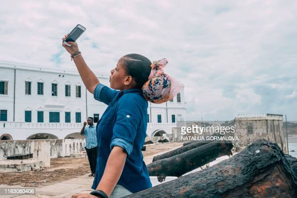 "Tourist takes a selfie at the Cape Coast Castle on August 18, 2019. - African-American visitors are flocking to Ghana as it marks the ""Year of..."
