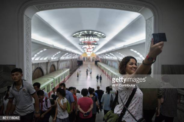 TOPSHOT A tourist takes a selfie during a visit to a subway station in Pyongyang on July 23 2017 The Westerners lined up before giant statues of...