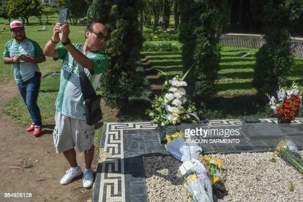 A tourist takes a selfie next to the grave of druglord Pablo Escobar on the 24th anniversary of his death at the Montesacro cemetery in Itagui near...