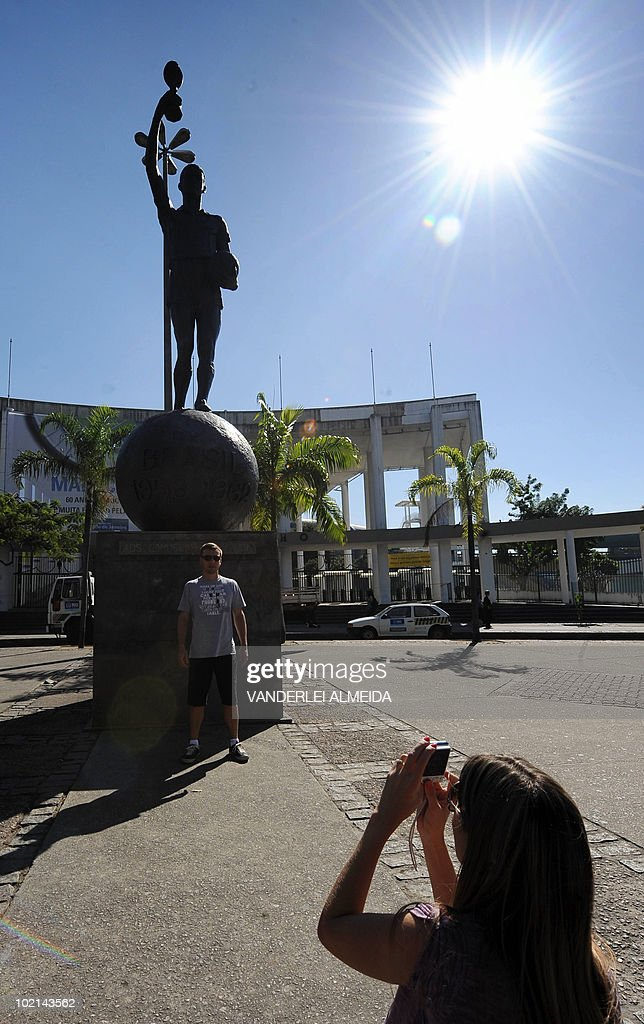 A tourist takes a snapshot in front of the statue depicting Brazilian footballer Hilderaldo Bellini --the team captain in the 1958 and 1962 World Cup that Brazil won-- outside the Maracana stadium, in Rio de Janeiro, on June 16, 2010. Today marks the 60th anniversary of the stadium --which real name is Mario Filho stadium-- which will soon be closed for refurbishment for the 2014 FIFA World Cup and the 2016 Olympic Games due to be held in this city. AFP PHOTO/Vanderlei ALMEIDA