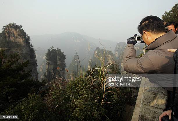A tourist takes a snapshot of the various peaks at the Zhangjiajie National Forest Park China's first national forest reserve which covers an area of...