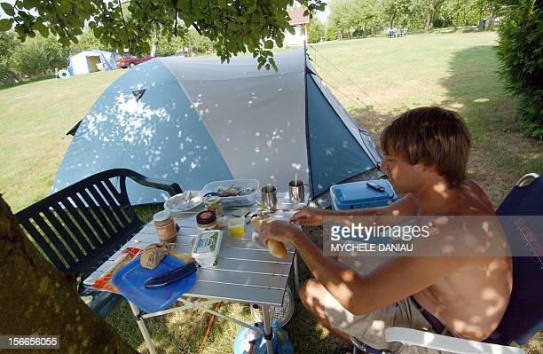 A tourist takes his breakfast 21 July 2006 at a camping in OuillyduHouley western France Un vacancier prend son petitdéjeuner le 21 juillet 2006 sur...