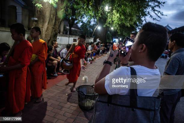 A tourist takes photographs as monks collect alms at a ceremony in Luang Prabang Laos on Monday Oct 22 2018 Laos's economy is set to expand at 7...
