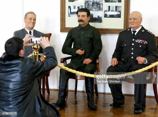 A tourist takes photographs of wax figures of world leaders attended the 'Yalta Conference' at the end of WWII at the Livadia Palace on March 13 2014...