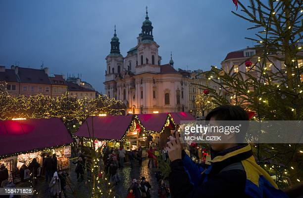 A tourist takes picture of the traditional Christmas market at the Old Town Square in Prague on December 17 2012 AFP PHOTO/MICHAL CIZEK