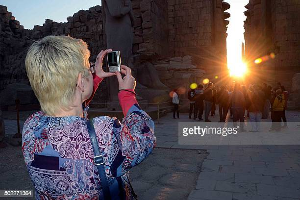 Tourist takes pictures as the sun rises behind the Temple of Karnak during the alignment of the winter solstice sunrise to the temple in the southern...