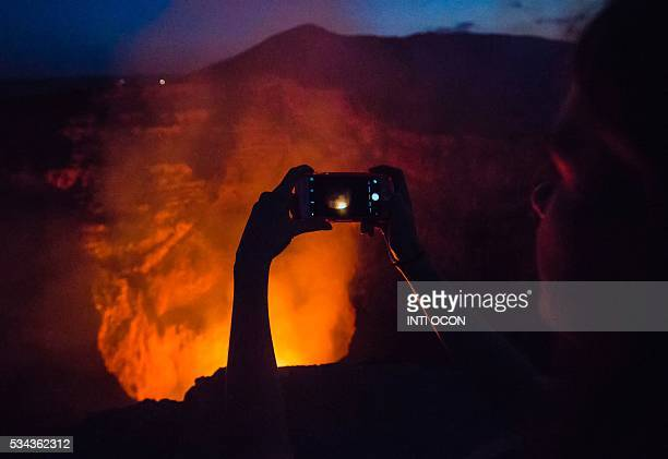 A tourist takes pictures of a lava lake inside the crater of the Masaya Volcano in Masaya some 30km from Managua on May 19 2016 Hundreds of tourists...