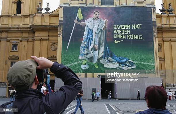 A tourist takes pictures of football player Franck Ribery of Bayern Munich on a city Nike advertising poster at the Odeonsplatz on August 09 2007 in...