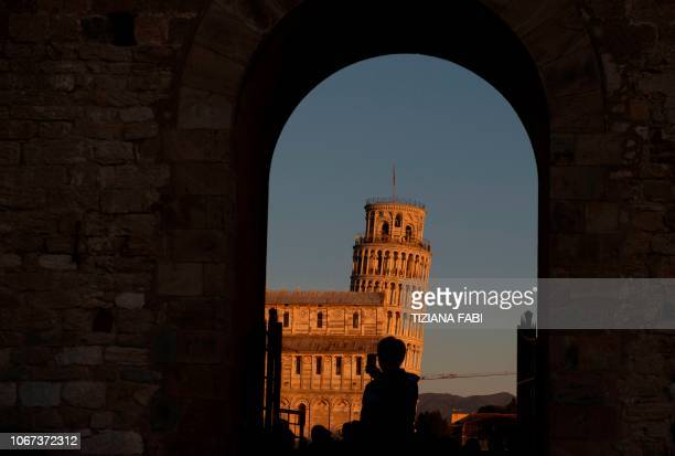 A tourist takes pictures of the Pisa Tower in Pisa on November 28 2018 The Leaning Tower of Pisa is now stable and has even straightened slightly...