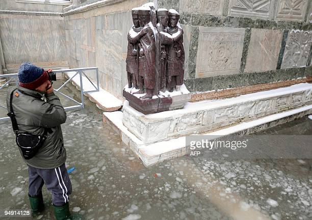 A tourist takes pictures on the flooded Piazza San Marco covered with snow on December 19 2009 in Venice The acqua alta a convergence of high tides...