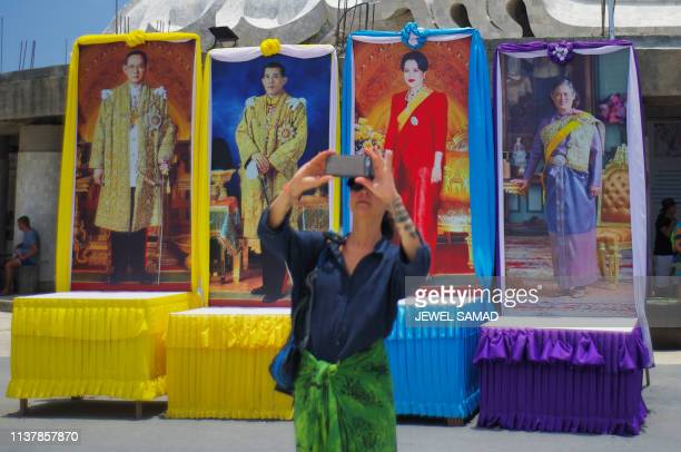 A tourist takes pictures while standing in front of portraits of the late Thai King Bhumibol Adulyadej King Vajiralongkorn Queen Sirikit and Princess...