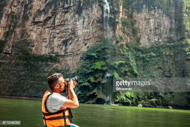 Tourist taking a photo at the Christmas Tree Waterfall in Sumidero Canyon