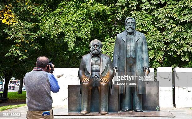 Tourist taking a photo of statue of Karl Marx and Friedrich Engels in Marx Engels Forum park in Berlin