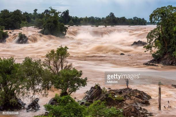 a tourist taking a photo of the rapid and majestic waterfall landscape at khone phapheng the famous waterfall in champasak, southern of laos - laotian culture stock pictures, royalty-free photos & images