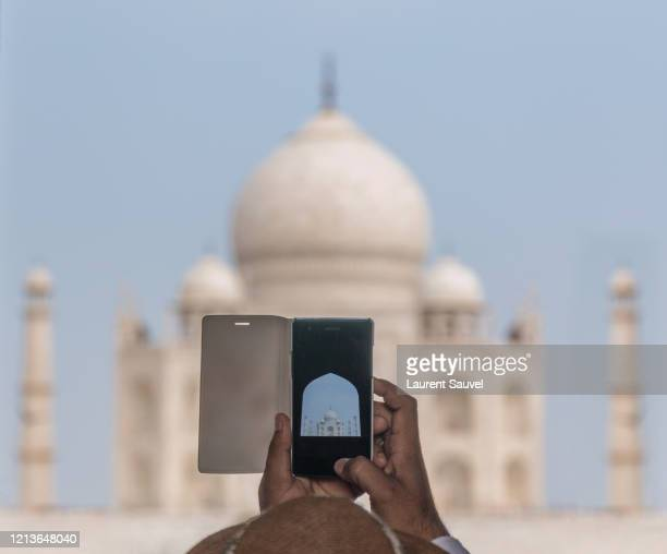 a tourist taking a photo of the taj mahal, agra, india with his mobile phone - laurent sauvel photos et images de collection