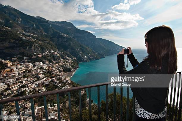 A tourist taking a photo of the town of Positano.