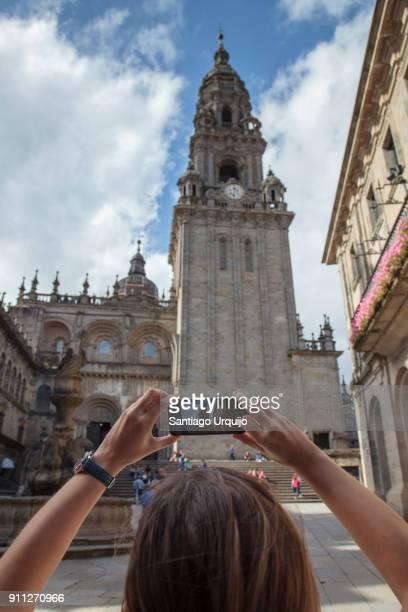 tourist taking a picture of santiago de compostela cathedral - cattedrale di san giacomo a santiago di compostela foto e immagini stock