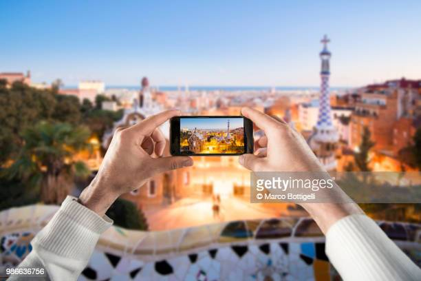tourist taking a picture of the park guell at dusk, barcelona. personal perspective view. - famous people stock photos and pictures