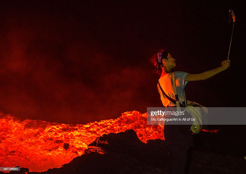 Tourist taking a selfie in front of the living lava lake in the crater of erta ale volcano, afar region, erta ale, Ethiopia on February 27, 2016 in Erta Ale, Ethiopia.