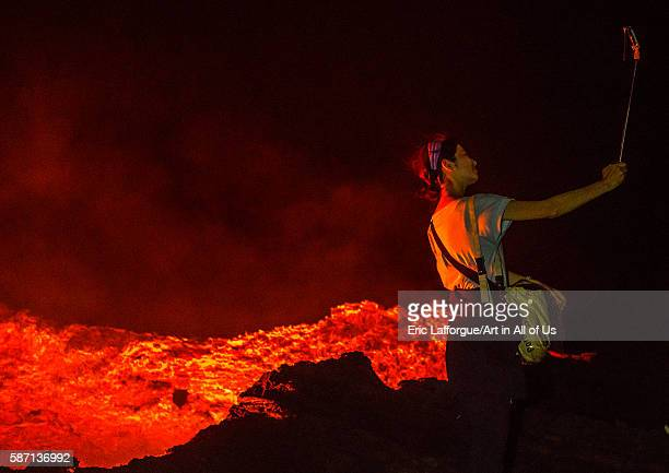 Tourist taking a selfie in front of the living lava lake in the crater of erta ale volcano afar region erta ale Ethiopia on February 27 2016 in Erta...