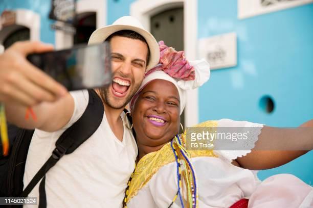 turista que toma um selfie com baiana (mulher brasileira tradicional) em bahia, brasil - turismo urbano - fotografias e filmes do acervo