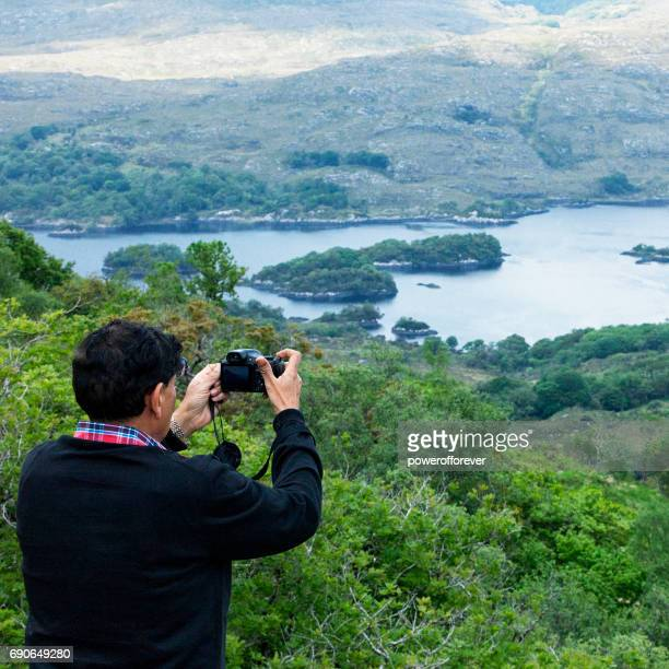 Tourist taking photo at Ladies View on the Ring of Kerry, Ireland