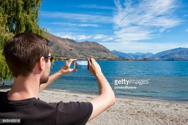 foto de tomada turísticas no lago wanaka da alpes do sul da nova zelândia - alpes do sul da nova zelândia - fotografias e filmes do acervo