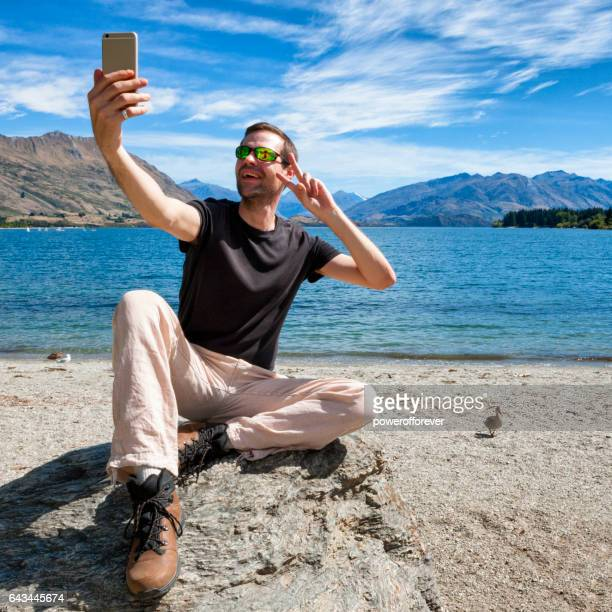 Tourist taking photo at Lake Wanaka in the Southern Alps of New Zealand