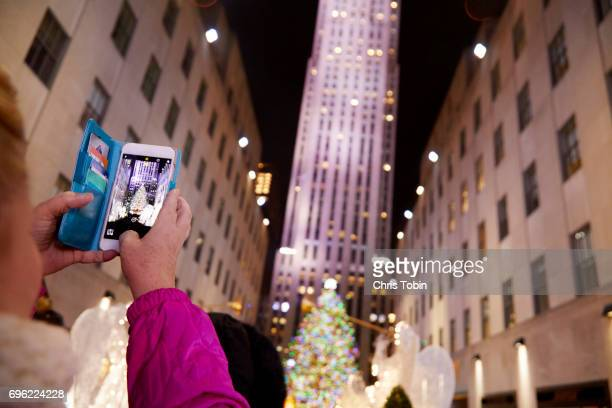 Tourist taking photo of city Christmas tree with smartphone