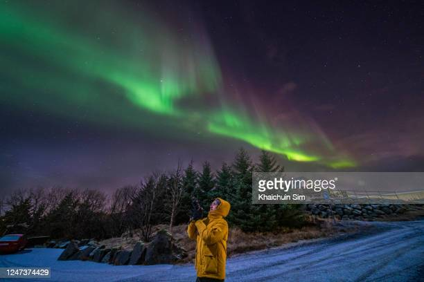 tourist taking photo of northern lights - iceland stock pictures, royalty-free photos & images