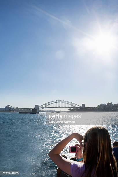 Tourist taking photo of Sydney Harbour Bridge.