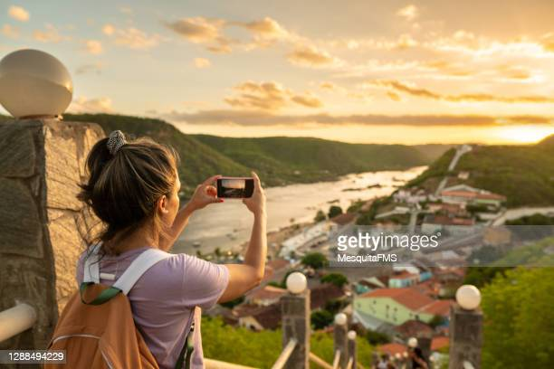 tourist taking photo of the aerial view of piranhas in alagoas - piranha stock pictures, royalty-free photos & images
