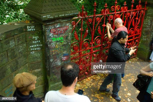 Tourist taking photograph of Strawberry Field in Liverpool