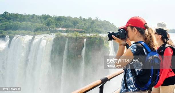 tourist taking photos of a huge waterfall from a bridge - waterfall stock pictures, royalty-free photos & images